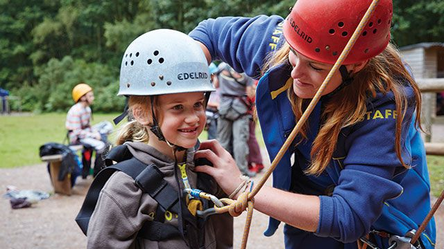 PGL Instructor adjusting a harness on a young Brownie