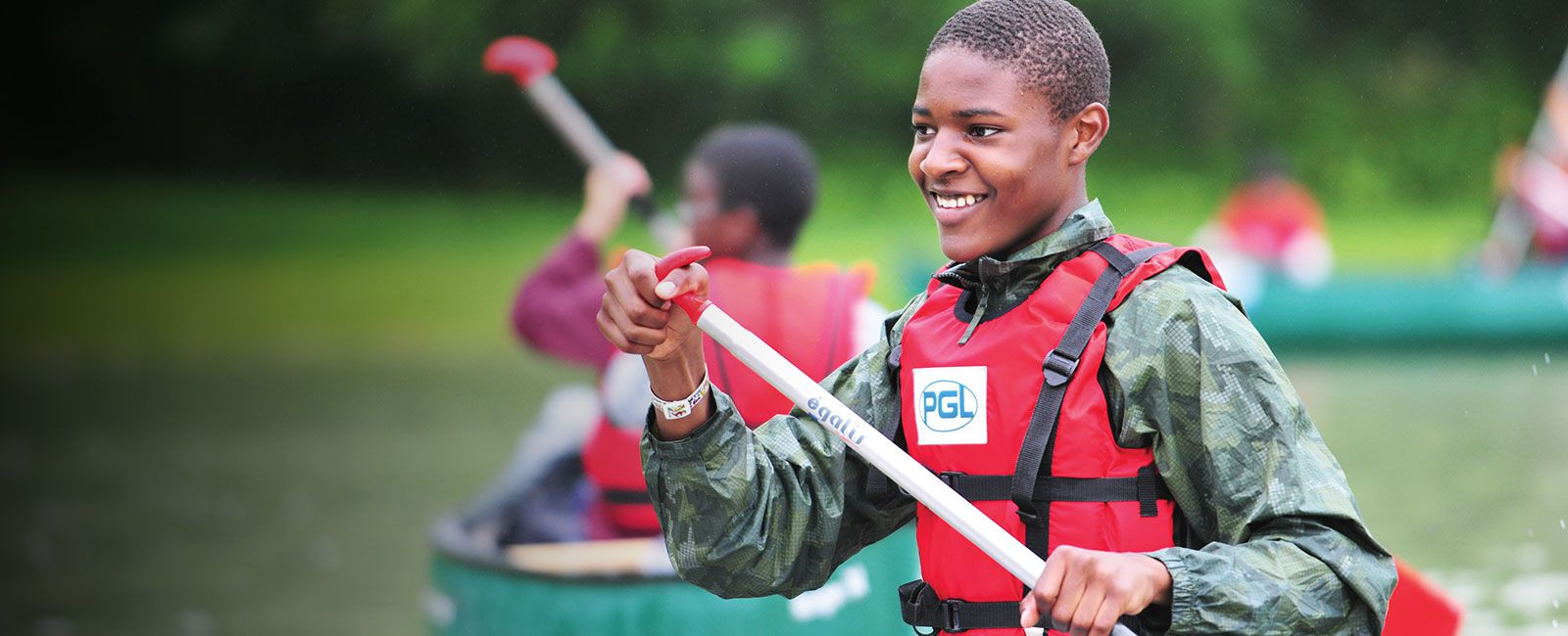 Young boy paddling a canoe across a lake at PGL
