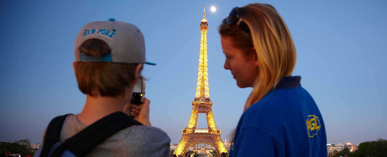 PGL Tour Leader with boy in front of Eiffel tower at night