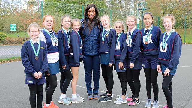 England Netball Champion Eboni Beckford-Chambers with a young netball team from St Bedes School
