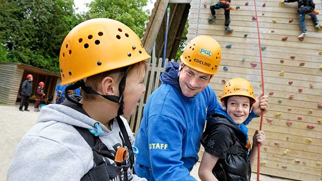 Children with instructor at the base of a climbing wall at PGL