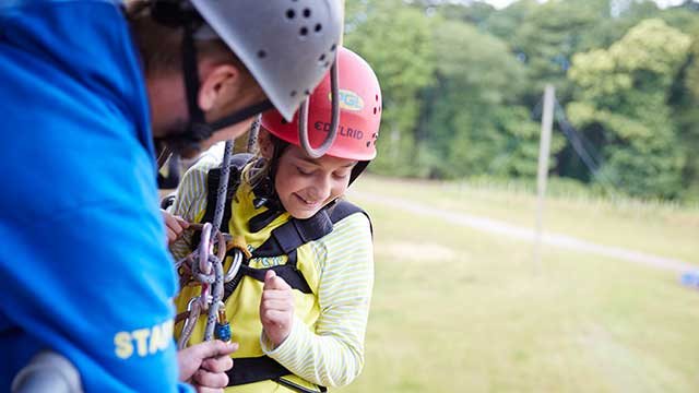 An instructor helping a Brownie abseil down a tower at PGL